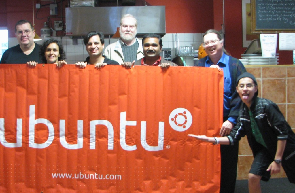 People at the Ubuntu Release Party behind an Ubuntu banner